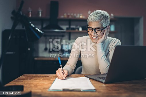 Smiling senior woman with laptop and documents in the evening