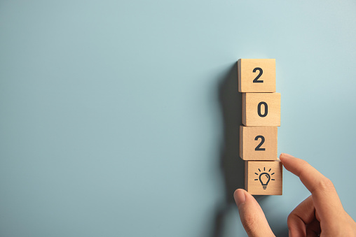 istock Creativity inspiration concepts, Woman hand arranging wood block with new year 2020 and lightbulb icon, planning ideas. 1168635188