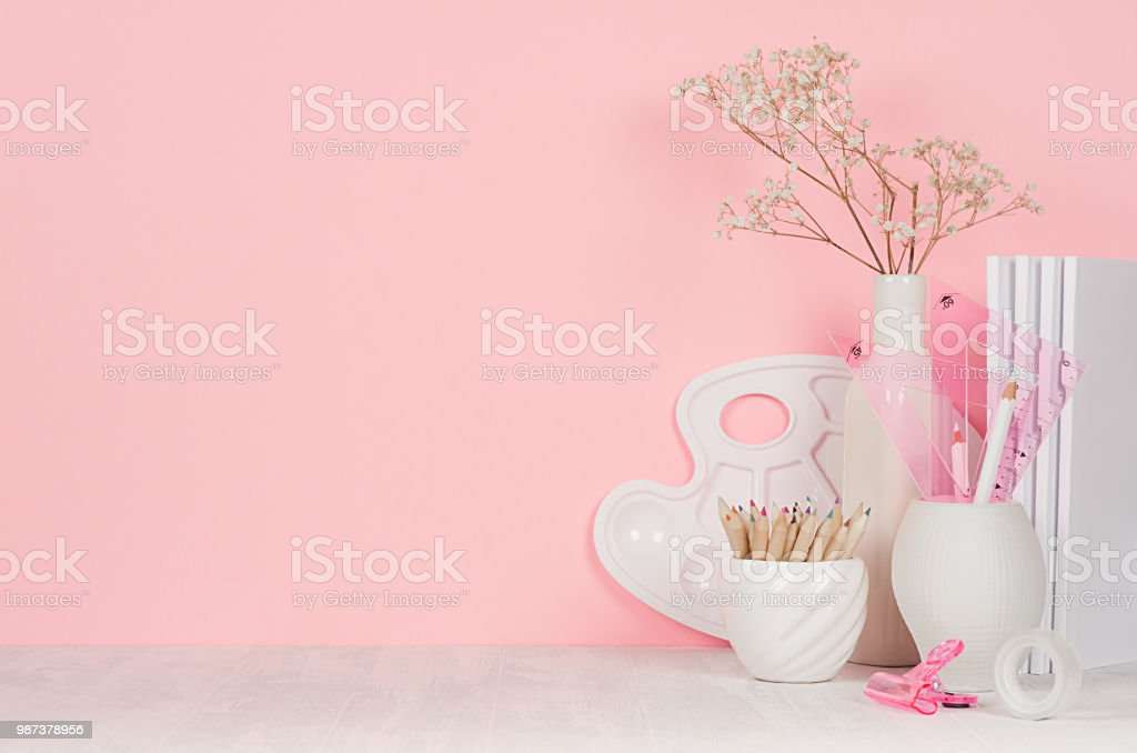 Creativity school background for girl's - white stationery, palette, pencils on soft pink wall and white wood desk. stock photo