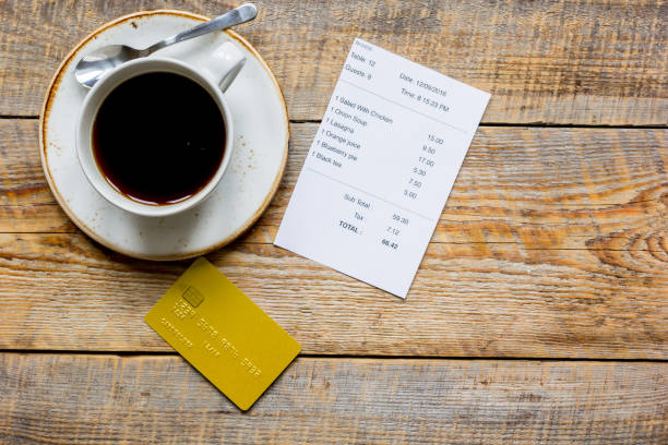credit card for paying, coffee and check on cafe wooden desk background top view mock up - receipt stock photos and pictures