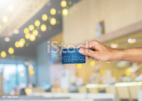 istock Credit card hand holding with blurred restaurant background 871864940