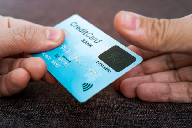 Credit card has built-in fingerprint scanner. Illustration of biometric payment security. One male hand is holding blue card and other touching scanner with thumb. stock photo