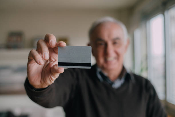 A credit card held by a senior man stock photo