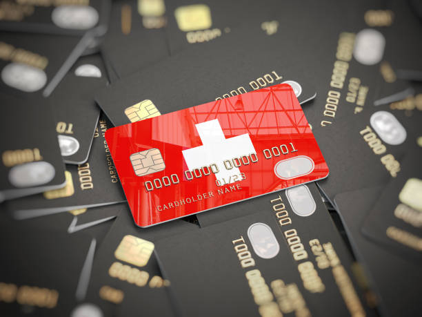 Credit card of swiss bank on the heap of other different black cards. Opening a bank account in Switzerland. stock photo