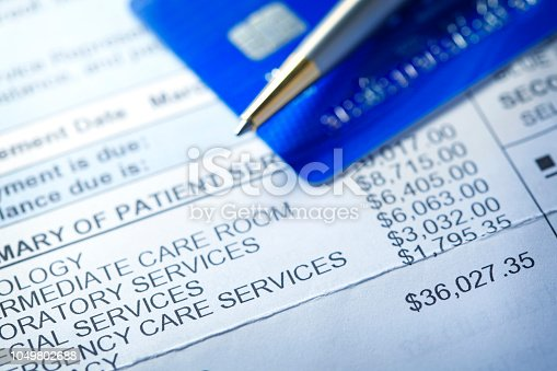 A hospital bill for $36,000 with a line item of various charges is photographed with a very shallow depth of field. A credit card and a ballpoint pen rest out of focus in the background.