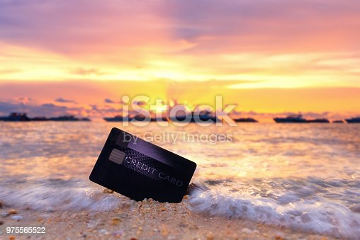 Credit card on the tropical beach in Pattaya at sunset,travel and holiday concept.