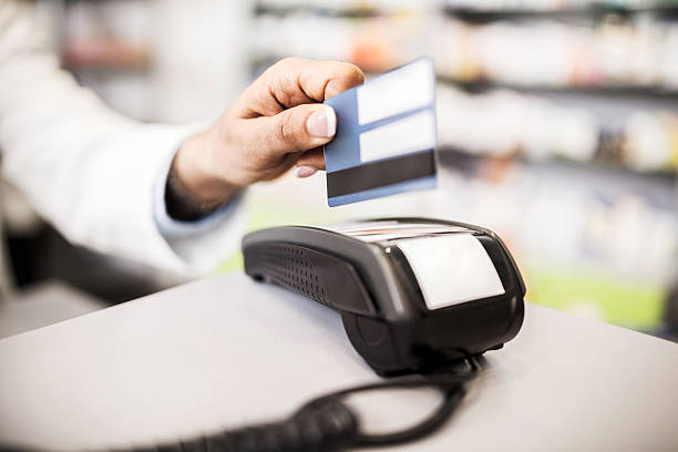 Credit card payment in pharmacy. Unrecognizable pharmacist putting a credit card into a credit card reader. smart card stock pictures, royalty-free photos & images