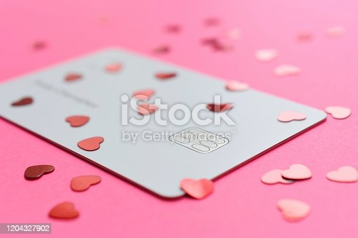 Credit card and hearts on a pink background