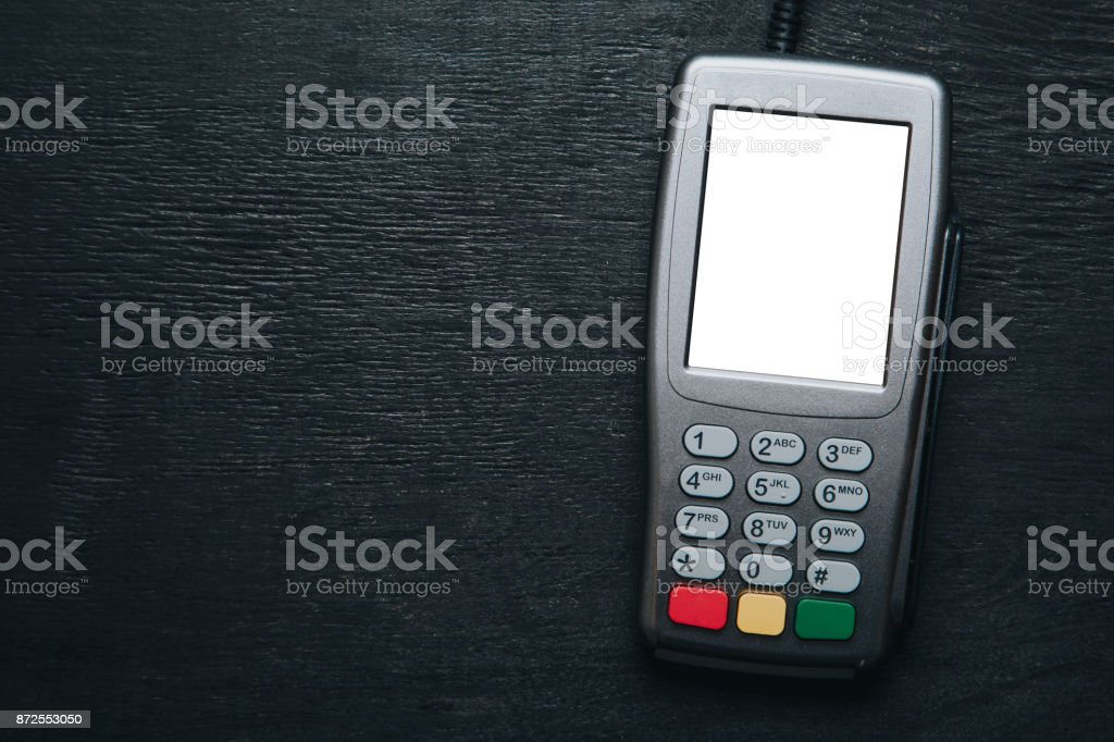 Credit card terminal on dark wooden desk stock photo