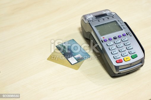 914593772istockphoto Credit card with payment terminal on wood desk 920998530