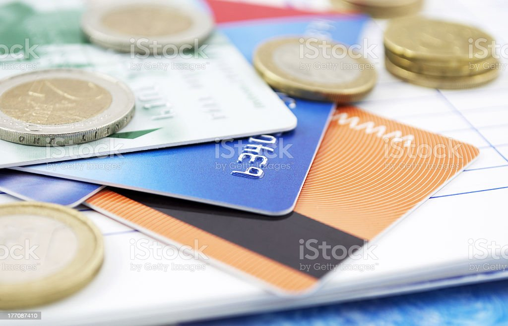 Credit cards and coins laying in a pile on a book royalty-free stock photo