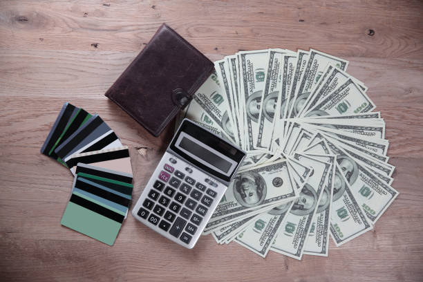 credit cards and dollar bills laid out on a wooden table.business background - disbursement stock pictures, royalty-free photos & images