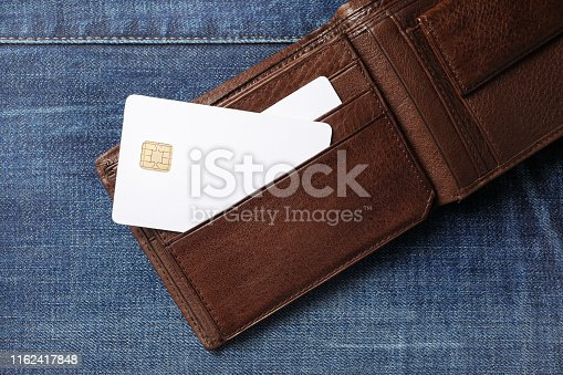 Blank white credit cards in leather wallet on denim background. Flat lay.