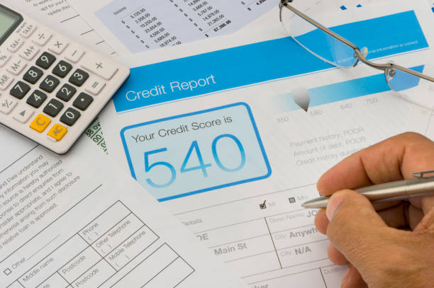 Credit report form on a desk Credit report form on a desk with other paperwork. There are also a pen, glasses and a calculator on the desk. Hand is holding pen negative emotion stock pictures, royalty-free photos & images