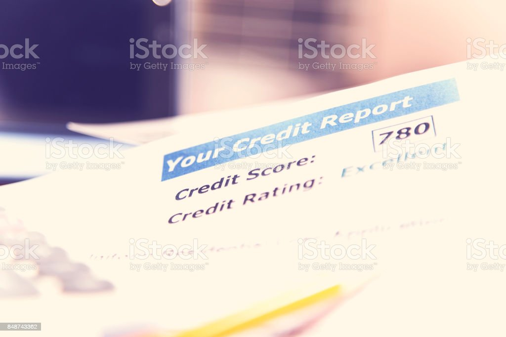 Credit report, loan documents, digital tablet, pencil, and calculator on desk. stock photo
