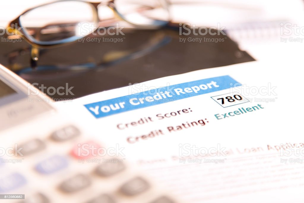 Credit report, score, loan documents, digital tablet, eyeglasses, and calculator on desk. stock photo