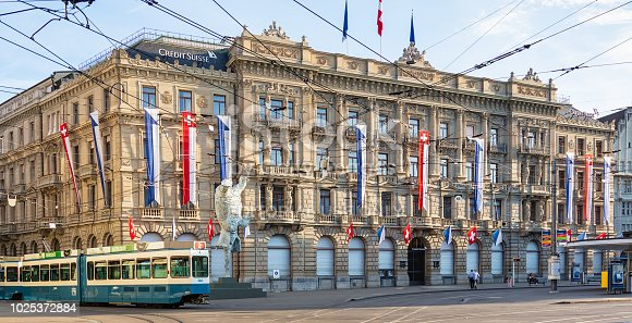 Zurich, Switzerland - August 1, 2018: Credit Suisse headquarters on Paradeplatz square, decorated with flags of Zurich and Switzerland, people on a tram stop at it. Credit Suisse Group AG is a Swiss multinational investment bank and financial services company founded and based in Switzerland.