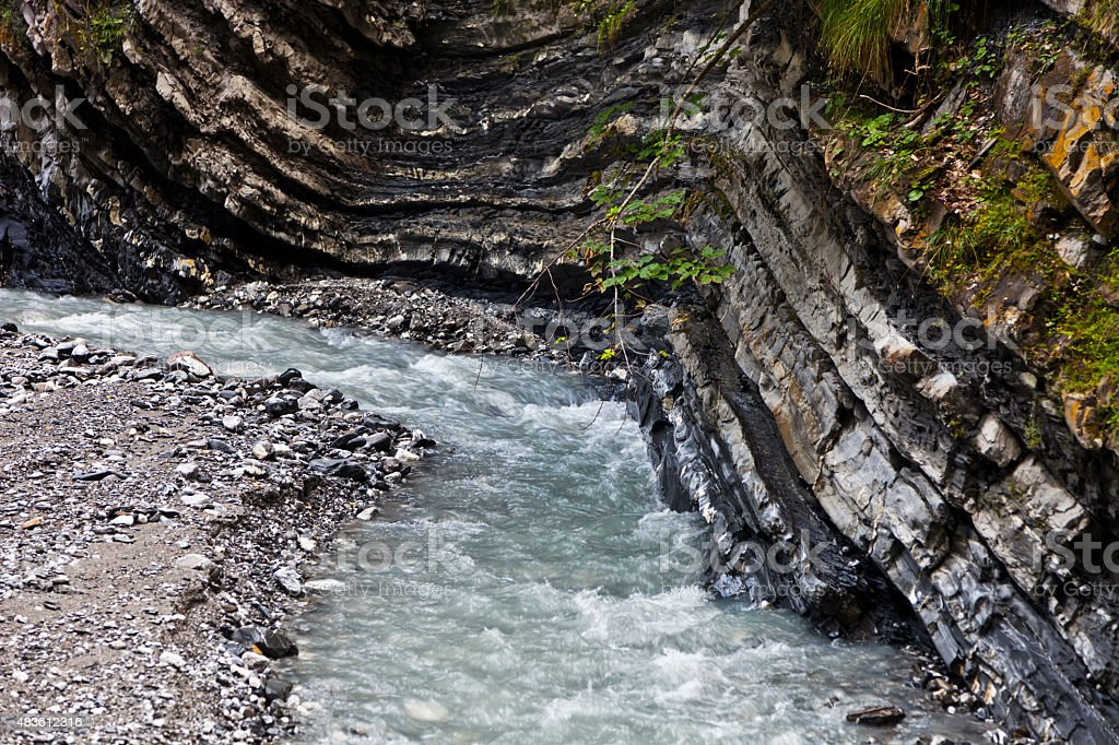 Creek Flowing along Layers of Rock in the Swiss Alps stock photo