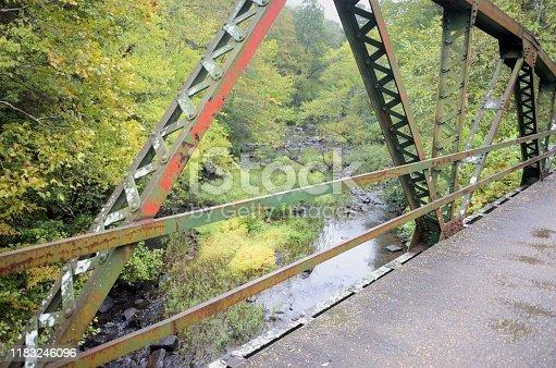 Looking off old metal truss bridge onto scenic river