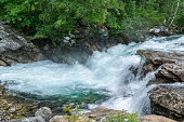 Creek high up in the Norwegian mountains with fresh turquoise water flushing rapidly through rocks