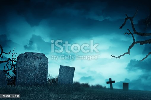 Creepy atmosphere in the cemetery with tombstone in the night, fog and trees that live twigs
