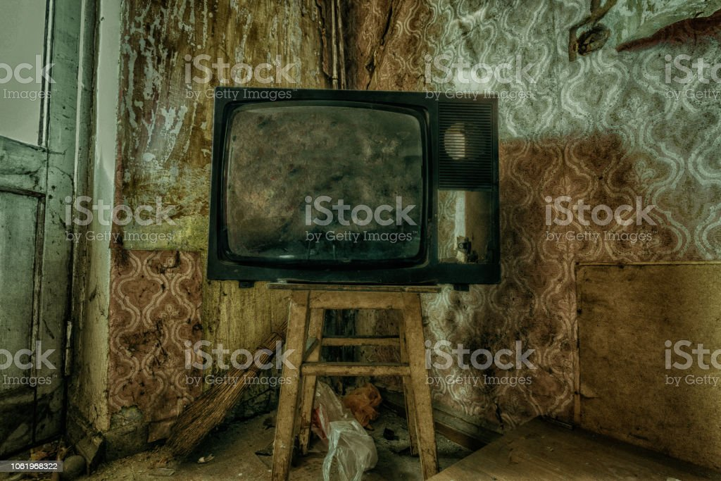 Creepy broken television in dirty room of abandoned house.