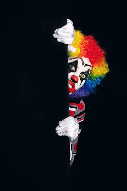Creepy Clown Around The Corner A creepy clown peeking around a dark corner. creepy stalker stock pictures, royalty-free photos & images