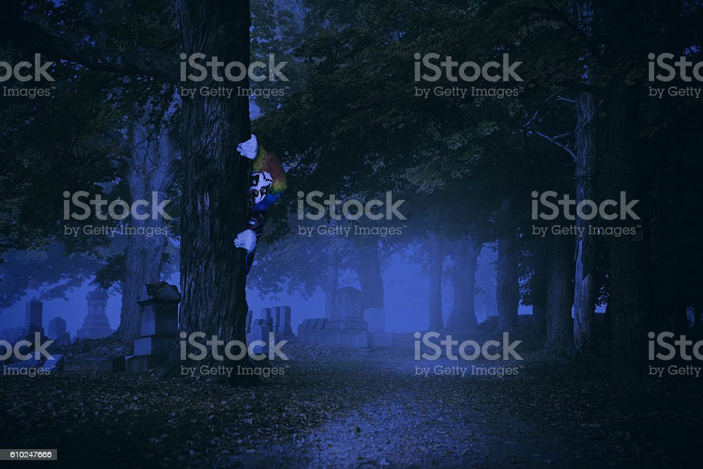 Creepy Clown Hiding In Wooded Cemetery stock photo