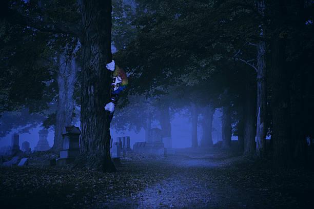 Creepy Clown Hiding In Wooded Cemetery - foto de stock