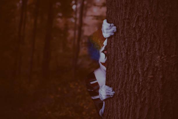 Payaso escalofriante leerlo alrededor de árbol - foto de stock