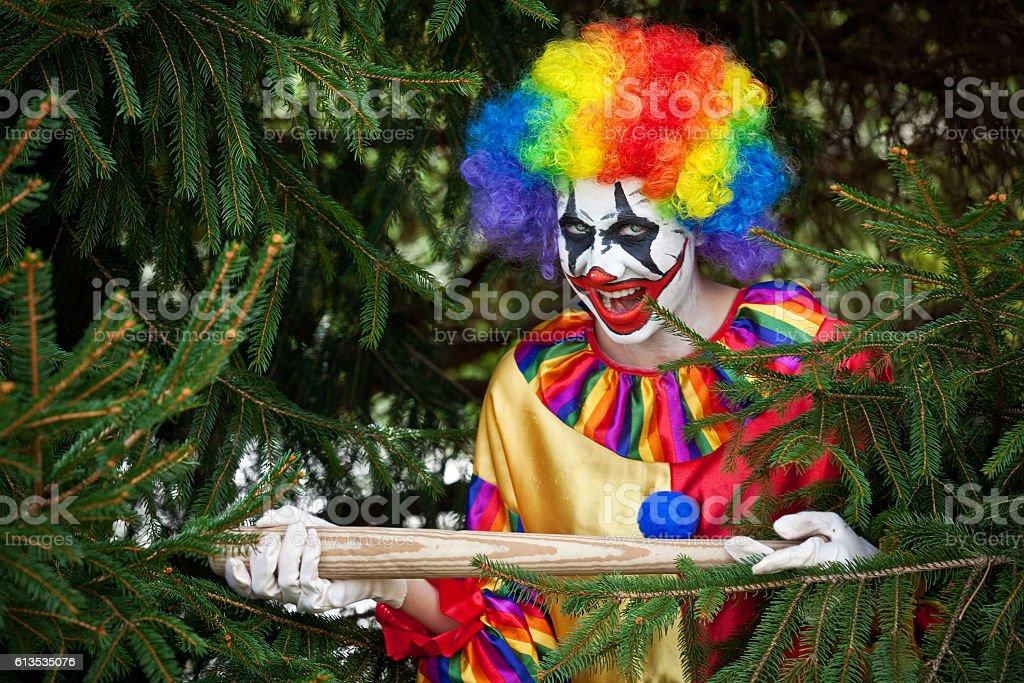 Creepy Clown With Bat Hiding In Pine Tree stock photo