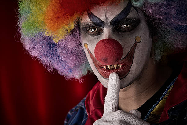 Creepy Clown with fingers on lips stock photo