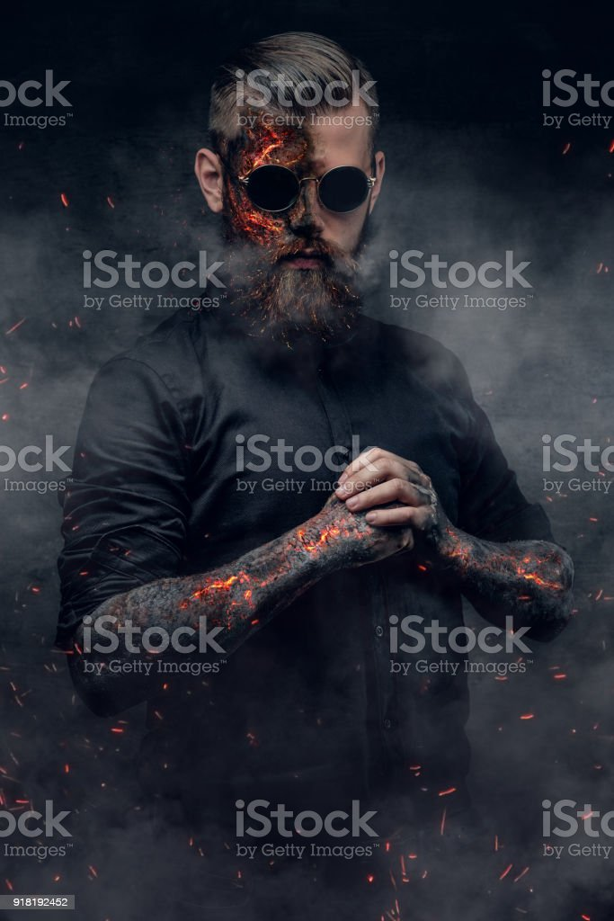 Creepy demonic male in a fire sparks and smoke. stock photo