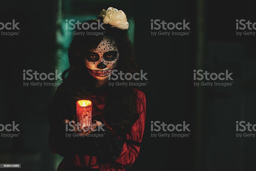 Creepy girl Halloween girl holding glowing candle in dark house Blood Stock Photo