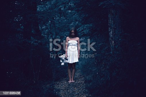 Creepy Girl with Teddy Bear Stand Alone in Dark Forest