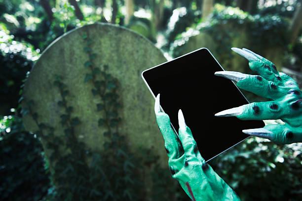 gruselige halloween-monster hände mit digitalen tablet am friedhof - halloween grabsteine stock-fotos und bilder