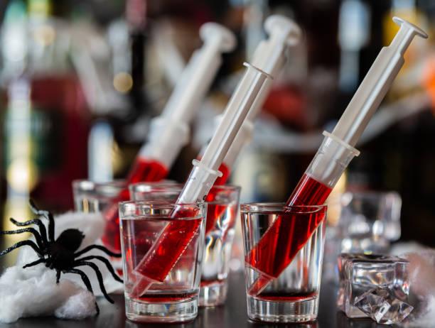 coquetéis de festa de dia das Bruxas assustador com seringas de xarope de grenadine como sangue, tiro de bebidas na festa - foto de acervo