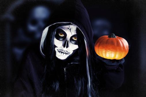 A creepy skeleton holding a pumpkin for Halloween.