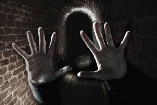 Creepy hand in the dark cell stock photo