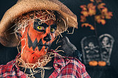 A person painted as a scary pumpkin scarecrow with a crow on the shoulder.