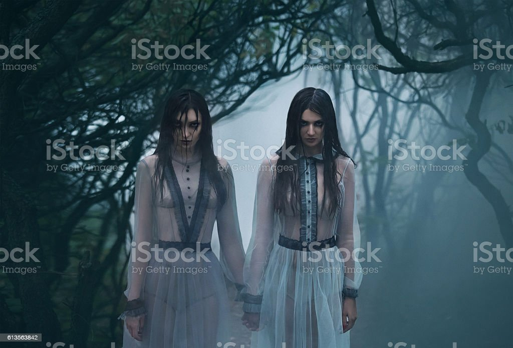 Creepy lady with long black hair looking at you stock photo