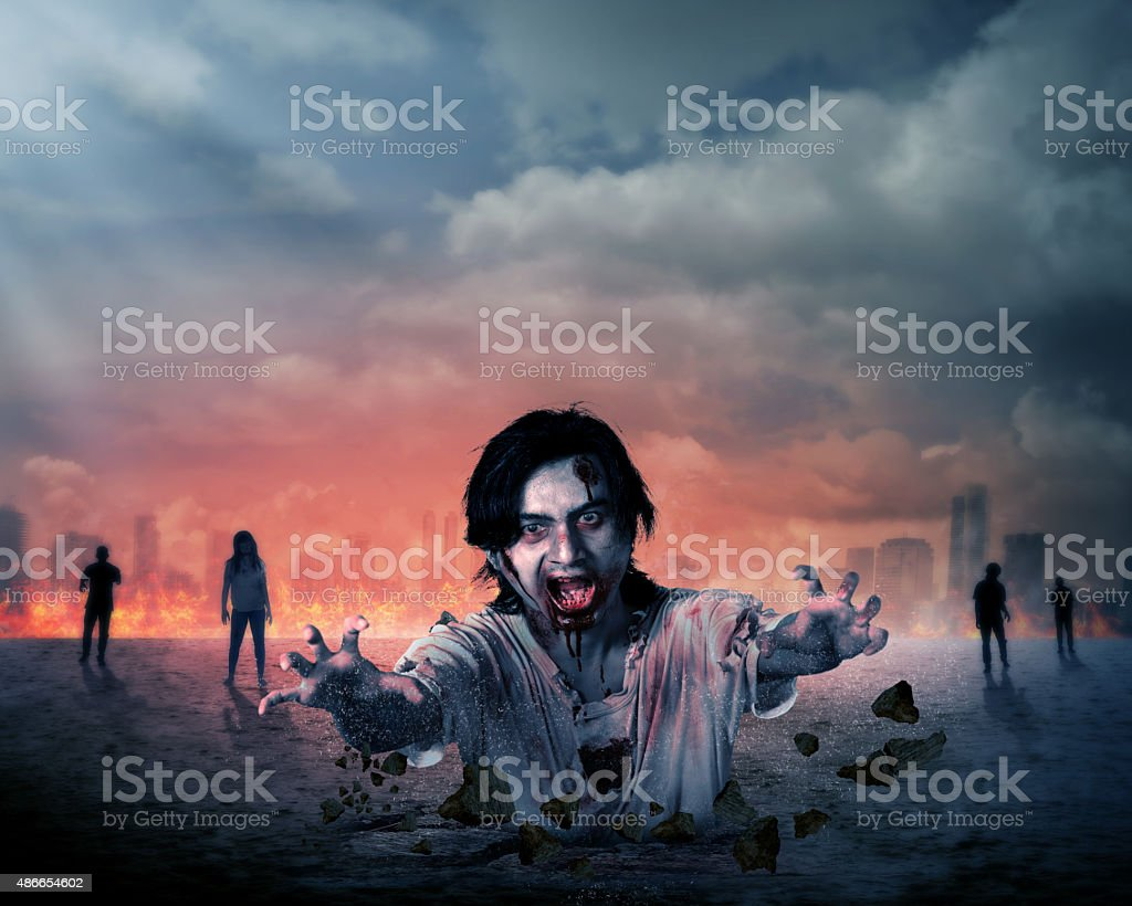 Creepy male zombie out from the ground stock photo