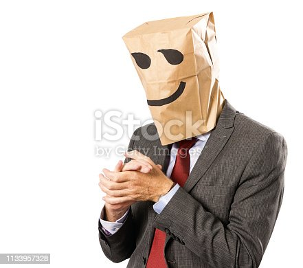 A businessman disguised by a paper-bag mask with a sly smile drawn on it rubs his hands together like a gleeful villain.