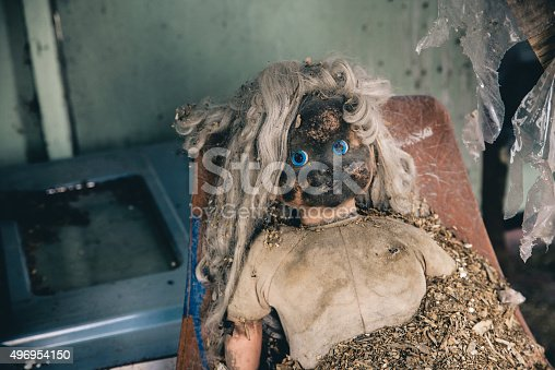 A creepy old doll with it's face burned off in an old abandoned building.