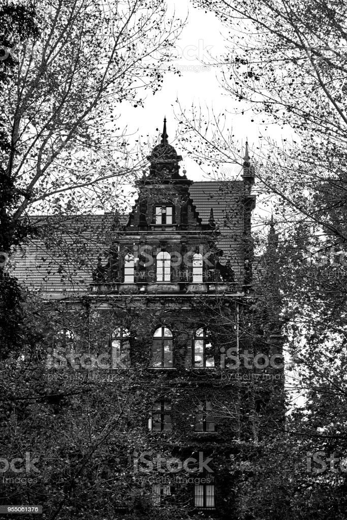 Creepy old house against the blue sky. Black and white stock photo