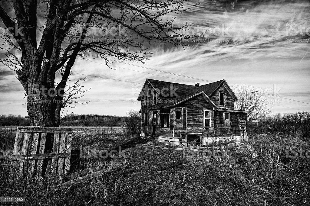 Creepy Old House Black and white photo of an old scary abandoned farm house that is deteriorating with time and neglect. Abandoned Stock Photo
