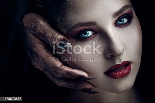 Demon touching face of young beautiful woman. Halloween theme.