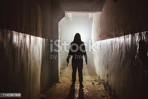 Creepy silhouette with knife  in the dark abandoned building. Horror about maniac concept.