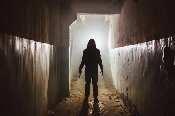 silueta espeluznante con cuchillo en el oscuro edificio abandonado. horror sobre el concepto maniático - halloween movie fotografías e imágenes de stock
