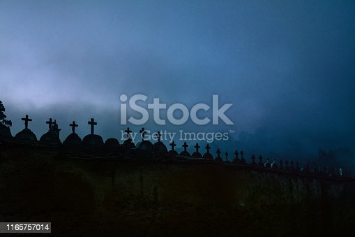 Creepy spooky graveyard atmosphere in the cemetery with tombstone and crosses in the foggy night.